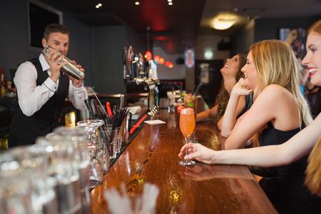 Knappe barman maken van cocktails voor mooie vrouwen in een stijlvolle bar