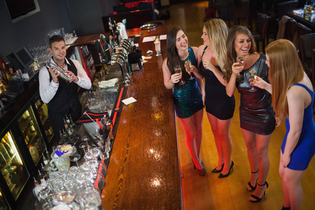 shaking out: Gorgeous women having cocktails together in a classy bar