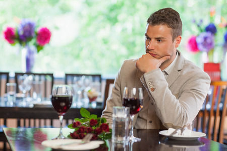 stood up: Handsome man waiting for his girlfriend with a bouquet in a classy restaurant
