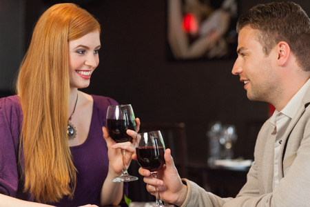 Handsome man having glass of wine with his gorgeous girlfriend in a classy restaurant photo
