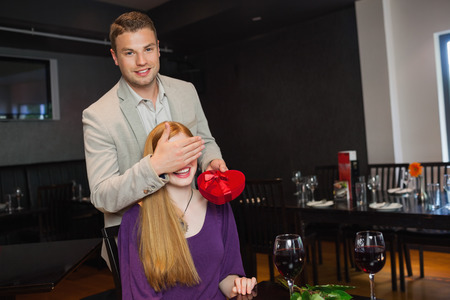Handsome man offering present to his pretty girlfriend during dinner in a classy restaurant photo
