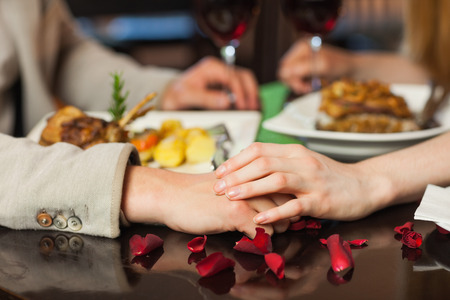 during: Close up on loving couple holding hands during romantic dinner