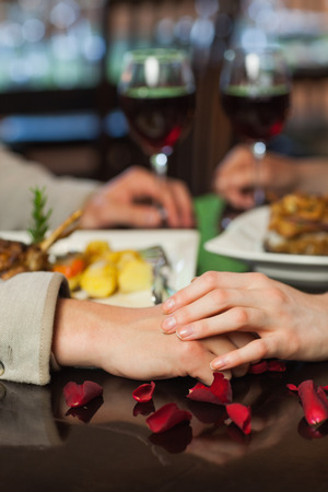 Close up on couple holding hands during dinner in a romantic restaurant