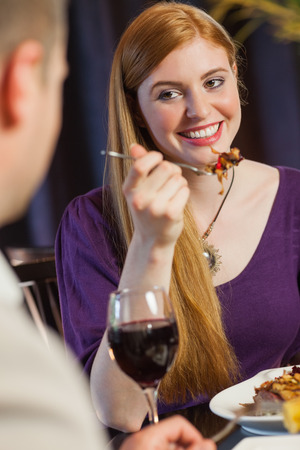 Pretty woman smiling at her husband during dinner in a classy restaurant photo