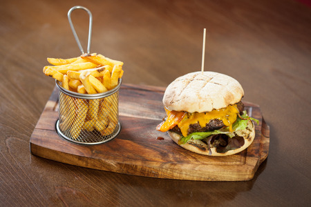 gourmet burger: Close up on a cheese burger and french fries served in classy restaurant on a wooden board