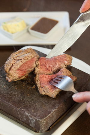 sizzling: Medium rare steak sizzling on hot stone plate being sliced served in classy restaurant