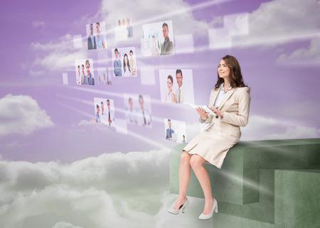 Cheerful businesswoman using futuristic interface while cloud computing photo