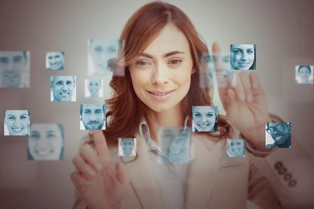 Businesswoman touching digital interface showing human faces photo