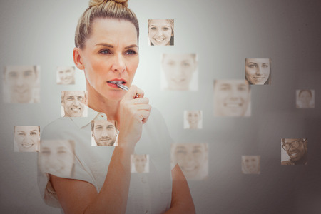 Serious businesswoman encircled by digital interface showing human faces photo