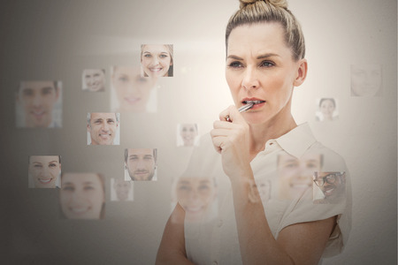 Stern businesswoman encircled by digital interface showing faces photo