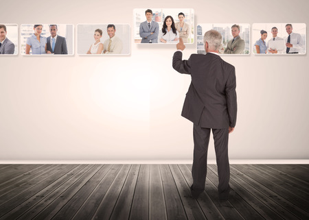 among: Businessman selecting business people digital interface among group of pictures