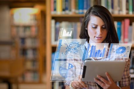 Hübsche Studentin arbeitet an ihrem futuristischen Tablette in einer Bibliothek Standard-Bild - 26738532