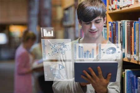 Young man studying on his futuristic tablet in a library photo