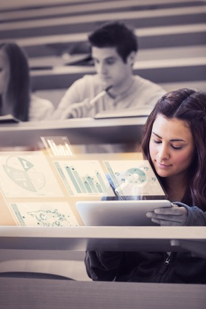 Student analysing graphs on her futuristic tablet computer in lecture hall photo