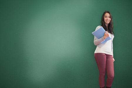 estudiantes universitarios: Brunette sonriente celebración portátil posando fondo verde Foto de archivo