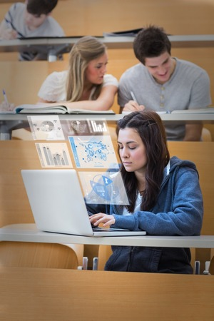 Pretty brunette studying on her digital laptop in lecture hall photo