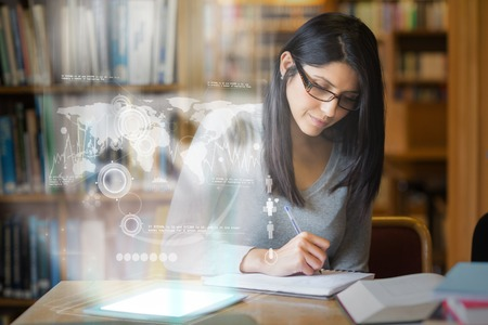 student studying: Serious mature student studying international trade on digital interface in university library Stock Photo