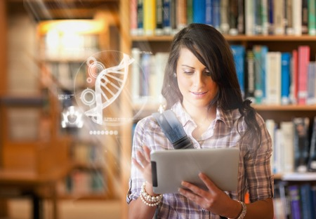 Pretty student using futuristic interface to learn about science from digital tablet standing in college library photo