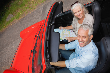 High angle view of smiling mature man having a ride with his wife in red convertible  photo