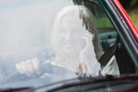 Cheerful mature woman on the phone driving red cabriolet on sunny day photo