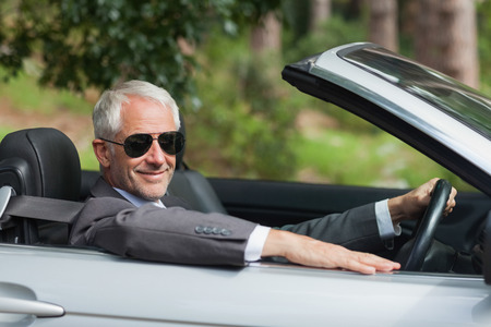 wealthy lifestyle: Smiling mature businessman driving classy cabriolet on sunny day