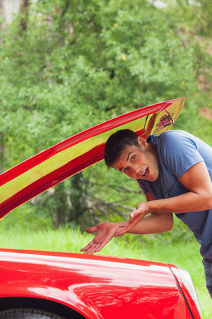 breaking down: Lost young man checking his car engine after breaking down during a ride in forest Stock Photo