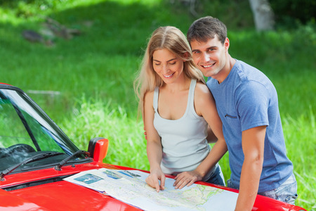 Cheerful young couple reading map on their cabriolet bonnet on a sunny day photo