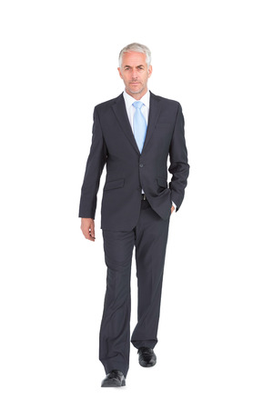 白い背景の上のカメラに歩くビジネスマン