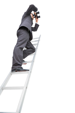 corporate vision: Low angle view of businessman standing on ladder using binoculars against white background Stock Photo