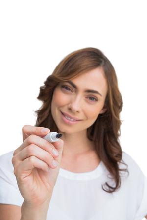Smiling businesswoman holding whiteboard marker on white background photo