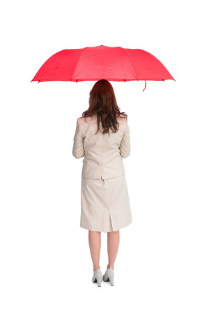 Businesswoman standing back to camera holding red umbrella against white background photo