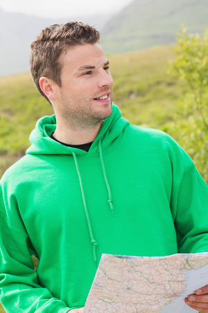 adventuring: Athletic man holding a map and looking ahead in the countryside