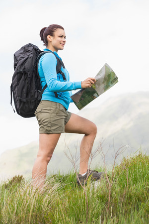 Attractive hiker with backpack walking uphill holding a map in the countryside photo
