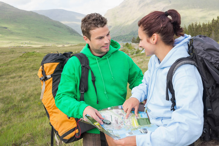 Happy couple resting after hiking uphill and consulting map in the countryside photo