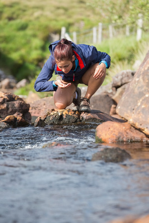adventuring: Hiker bending to take a drink from the stream in the countryside