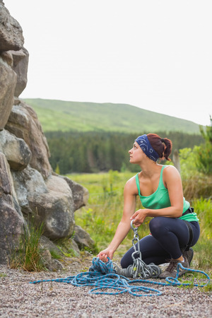 Pretty rock climber looking up at her challenge in the countryside photo