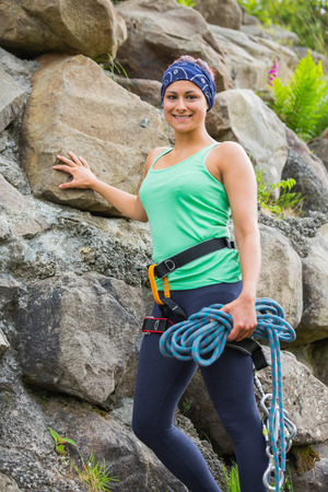 Attractive female rock climber smiling at camera leaning on rock face photo