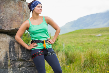 Pretty female rock climber leaning on rock face looking away in countryside photo