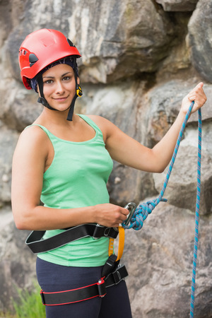 adventuring: Pretty rock climber about to start her climb by rock face Stock Photo