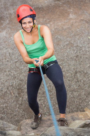abseiling: Smiling girl abseiling down rock face looking up at camera Stock Photo