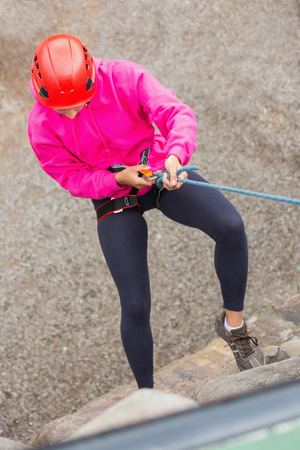 abseiling: Fit girl abseiling down rock face wearing pink jumper Stock Photo