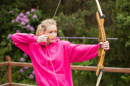 Concentrating blonde practicing archery at the range photo