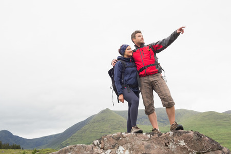 Couple standing on a rock looking at the mountains on a hike in the countryside photo