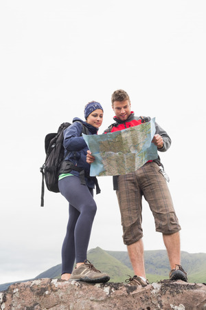 Couple standing on a rock reading map on a hiking trip photo