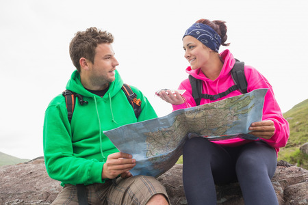 Couple using map and compass sitting on a rock during their hike photo