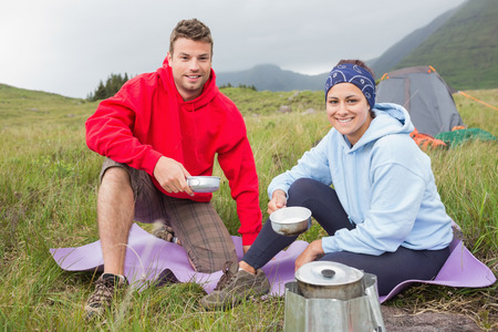 Couple cooking outside on camping trip smiling at camera in the countryside photo