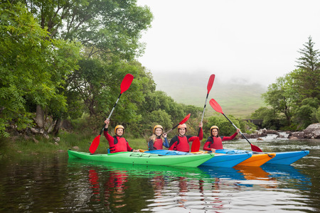 adventuring: Friends kayaking together cheering at camera in a lake in countryside