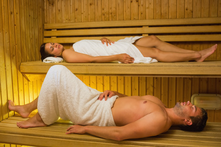 Calm couple relaxing in a sauna lying down wearing towels photo