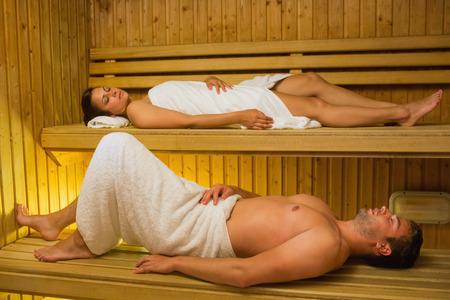 sauna: Calm couple relaxing in a sauna lying down wearing towels