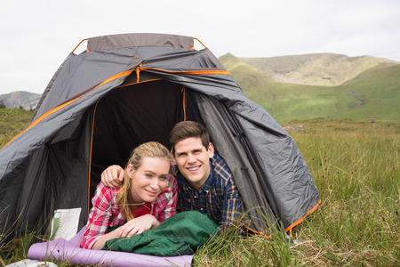 Happy couple lying in their tent and looking at camera in the countryside photo